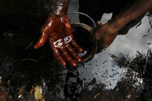 A man samples crude oil at the bank of a polluted river in Bidere community in Ogoniland in Nigeria's delta region August 20, 2011. Picture taken August 20, 2011. REUTERS/Akintunde Akinleye